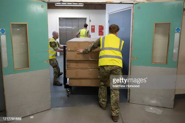 Hospital beds are moved into the Dragon's Heart hospital by members of the 1st Battalion The Rifles on April 9 in Cardiff, Wales. The Principality...