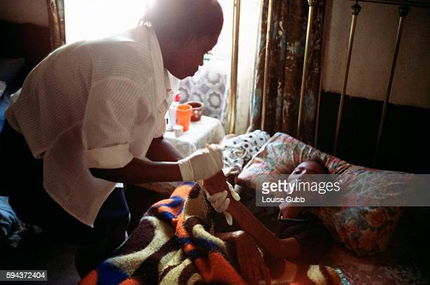 Hospital caregiver makes her first visit to Pumzile, age 20, who has contracted AIDS and is now bedridden, has partial paralysis in the legs, and has...