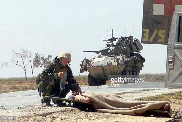 NU'MANIYAH IRAQ APRIL 2 Hospital Corpsman 3rd Class Christopher Pavicek from Escondido California provides aid to a wounded Iraqi soldier after a...