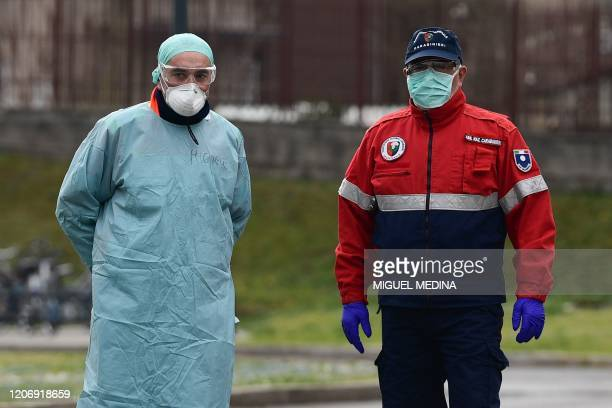 Hospital employee and a Carabinieri policeman wearing a protective mask stand at the entrance of a temporary emergency structure set up outside the...