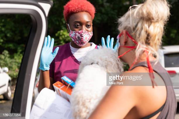 Hospital employee discharges a puppy at the curbside pet drop off at West Hills Animal Hospital as the city continues Phase 4 of re-opening following...