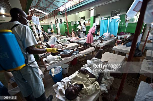 A hospital employee sprays disinfectant on a patient suffering from cholera at the Charles Colimon hospital in Petite Riviere on the Artibonite river...