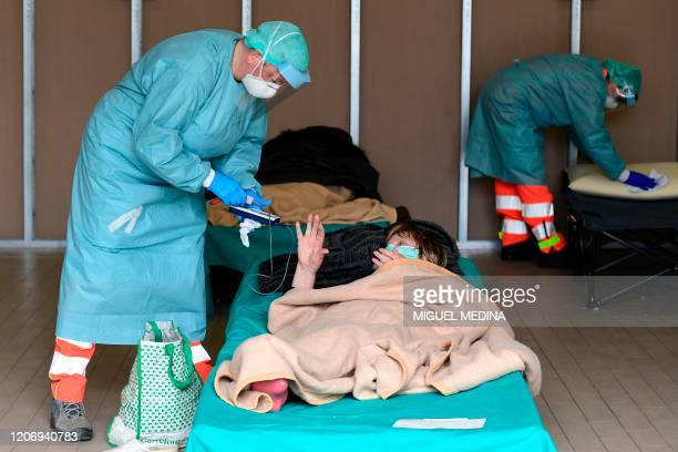 A hospital employee wearing a protection mask and gear tends to a patient lying in bed at a temporary emergency structure set up outside the accident...