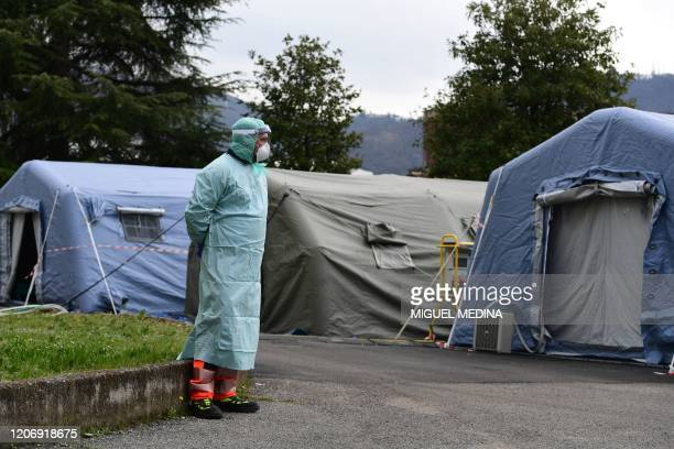 A hospital employee wearing a protective mask and gear stands by tents part of a temporary emergency structure set up outside the accident and...