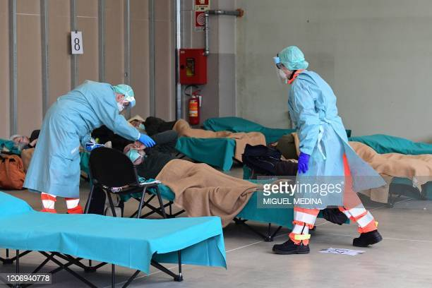 Hospital employees wearing a protection mask and gear tend to a patient at a temporary emergency structure set up outside the accident and emergency...