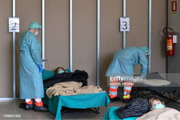 Hospital employees wearing protection mask and gear tend to patients lying in bed at a temporary emergency structure set up outside the accident and...