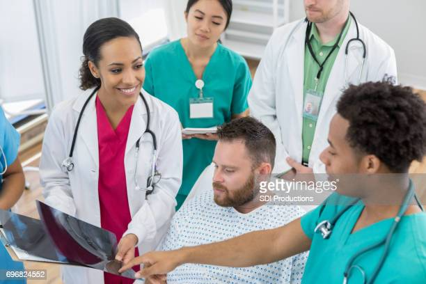 Hospital interns examine male patient's x-ray