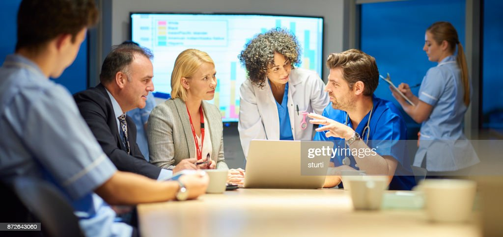 hospital management listening to doctor : Stock Photo