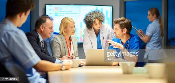 hospital management listening to doctor - healthcare and medicine stock pictures, royalty-free photos & images