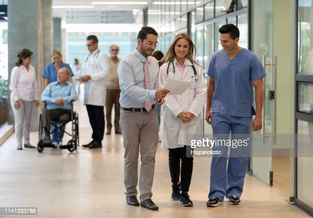 hospital manager showing a document to doctor and nurse all smiling - manager stock pictures, royalty-free photos & images
