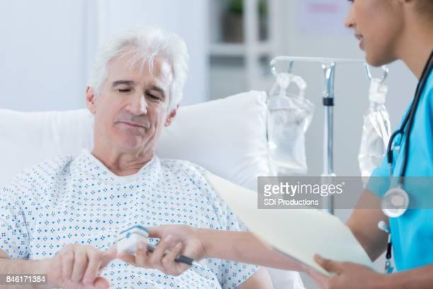 Hospital nurse checks patient's oxygen level