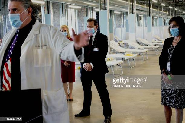 Hospital officials stand during a tour of a new Federal Medical Station at Palomar Hospital in Escondido, California on April 23, 2020. - The FEMA...