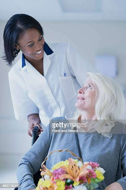 Hospital orderly pushing senior female patient in wheelchair