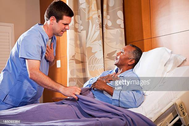 Hospital orderly talking with senior patient