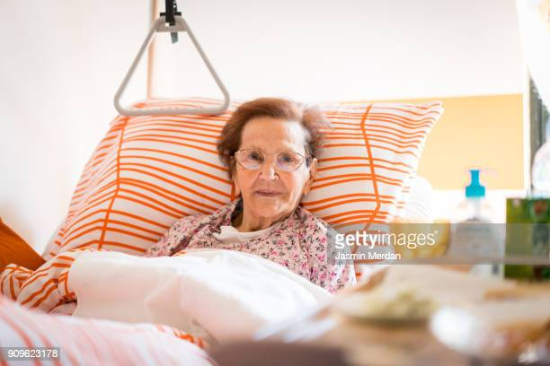 hospital patient hands to care - old woman in sick bed stock photos and pictures