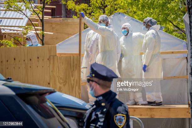 Hospital personnel seen pictured behind a barricade as they move bodies onto a refrigerated overflow trailer parked outside Wyckoff Hospital in...