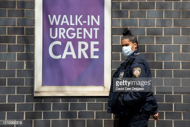 A hospital security guard wears a medical mask outside of Elmhurst Medical Center on April 15 in Queens borough of New York CityDuring his daily...