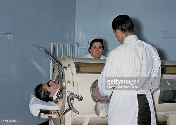 Hospital staff are examining a patient in a tank respirator iron lung during the Rhode Island polio epidemic 1960 The iron lung encased the thoracic...