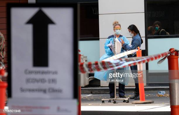 Hospital staff assist people waiting in line to be screened for COVID19 outside the Royal Melbourne Hospital on March 11 2020 in Melbourne Australia...