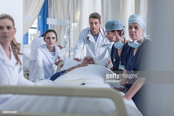 Hospital staff at bed with patient