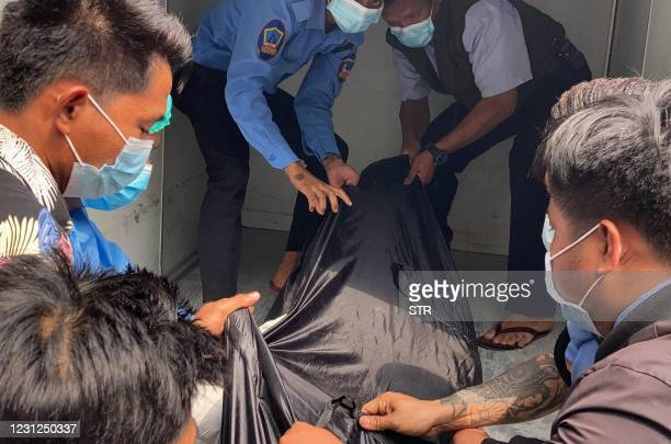 Hospital staff carry a body bag bearing the remains of Mya Thwate Thwate Khaing, a 20-year-old woman who was shot in the head last week during an...