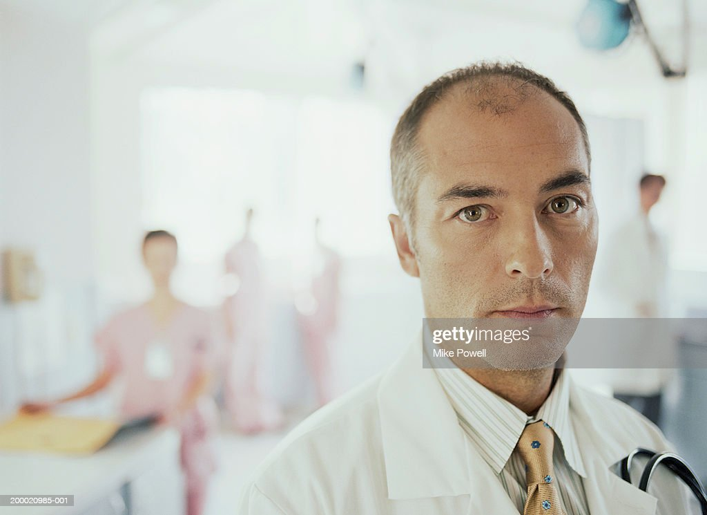 Hospital staff, focus on doctor in foreground : Stock Photo