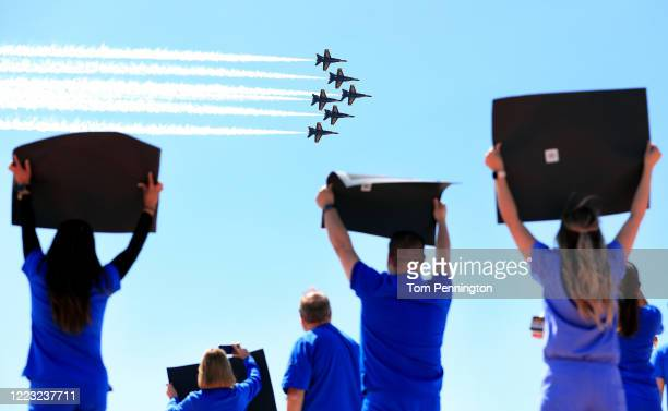 Hospital staff, including nurses, doctors, and administrators, cheer and look on as the United States Navy Blue Angels pass over Medical City Dallas...
