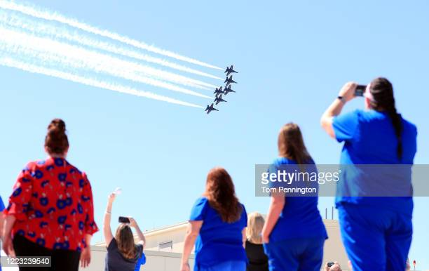 Hospital staff, including nurses, doctors and administrators, look on as the United States Navy Blue Angels pass over Medical City Dallas on May 06,...