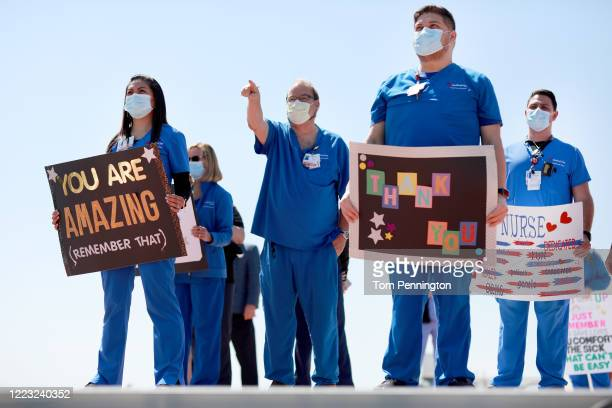Hospital staff, including nurses, doctors and administrators, look on in anticipation of the United States Navy Blue Angels flyover above Medical...
