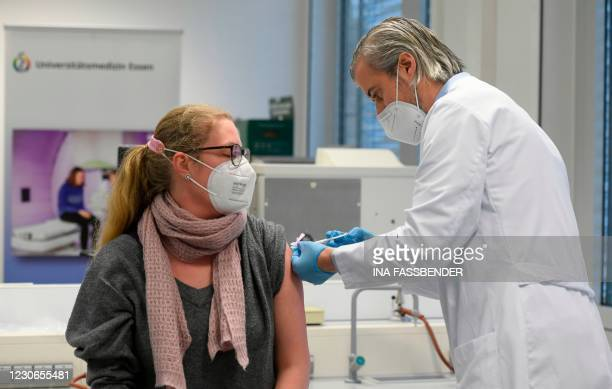Hospital staff member gets the injection with the Moderna Covid-19 vaccine at the corona vaccination centre at the University hospital in Essen,...