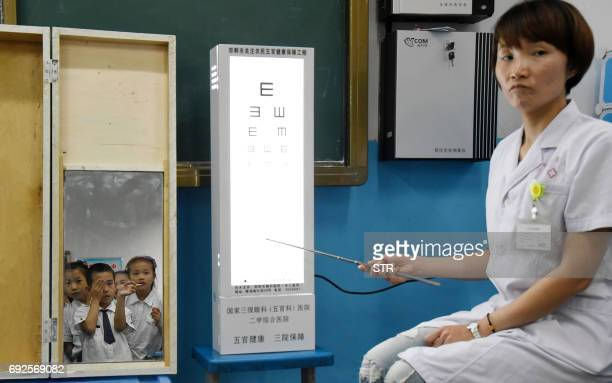 A hospital staff member performs vision tests on students at a primary school in Handan in China's northern Hebei province on June 5 2017 The...