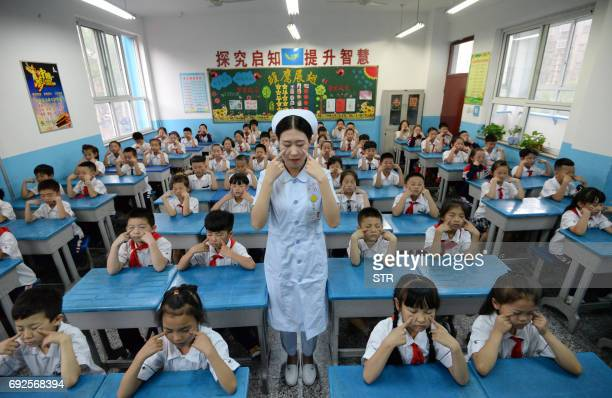 TOPSHOT A hospital staff member teaches primary school children how to do eye exercises at a primary school in Handan in China's northern Hebei...