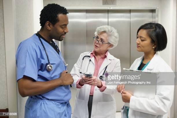 hospital staff talking in front of elevator - agenda eletrônica - fotografias e filmes do acervo