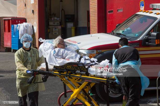 Hospital staff transfer a patient to an ambulance outside of Elmhurst Hospital on April 7 2020 in Queens New York