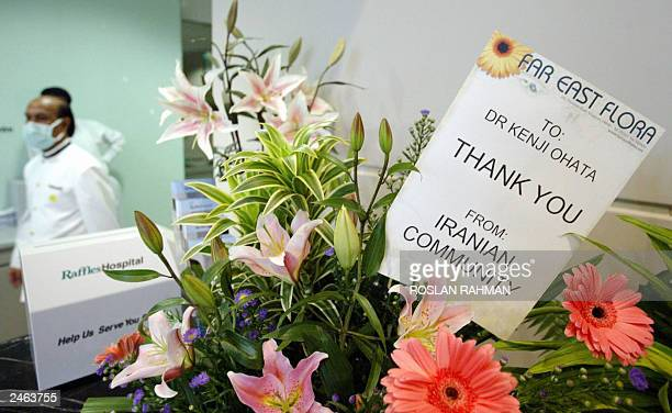 Hospital staff walk behind a bouquet of flowers sent by the Iranian community to thank the doctors of Raffles Hospital in Singapore 08 July 2003...