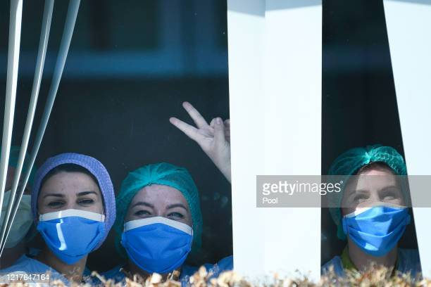 Hospital staff wearing protective masks look out of the window as King Philippe of Belgium visits the extended COVID19 unit at the University...