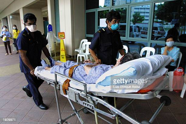 Hospital staff wheel in a suspected SARS victim April 14 2003 at Tan Tock Seng hospital in Singapore The hospital has become the epicenter for people...
