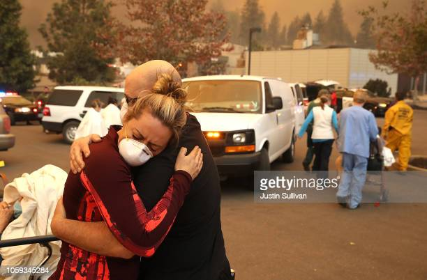 Hospital worker embraces her co-worker as they evacuate patients from the Feather River Hospital during the Camp Fire on November 8, 2018 in...