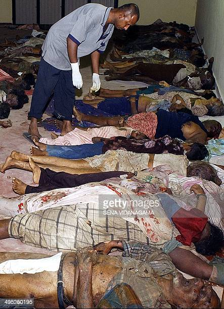 A hospital worker looks for identification documents on dead bodies at the Karapitiya hospital some 125 kms south of the Sri Lankan capital Colombo...