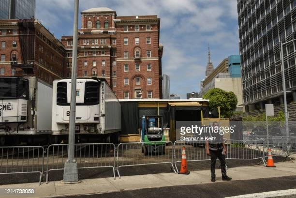 Hospital worker stands near to the loading dock where refrigerator trucks are parked at NYU Langone Hospital on May 22, 2020 in New York City. New...