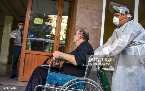 A hospital worker wearing a face mask and protective gear pushes a man in a wheelchair at the Grigor Lusavorich Medical Centre in Yerevan on May 29...