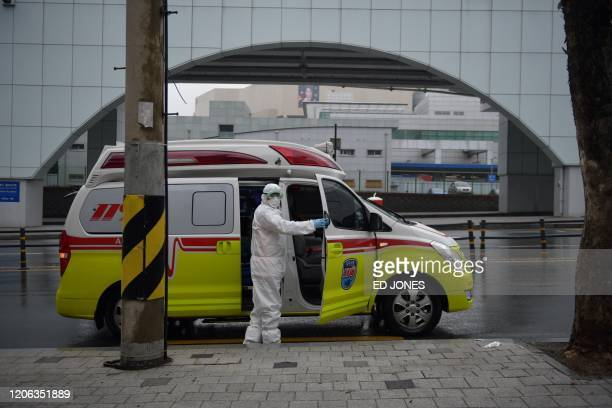 Hospital worker wearing protective equipment amid concerns about the spread of the COVID-19 novel coronavirus, stands next to an ambulance on a...