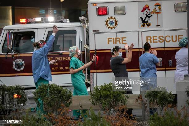 Hospital workers cheer as first responders pass by the Westchester Medical Center in a caravan of sirens and lights on April 14 2020 in Valhalla New...