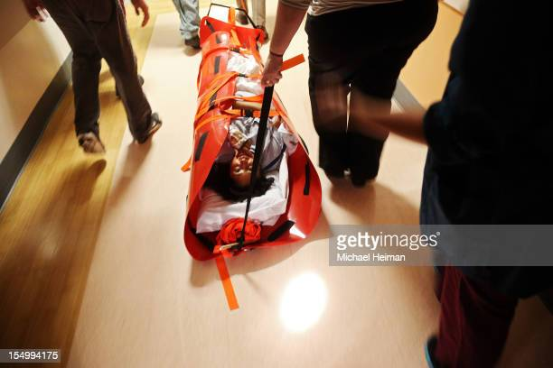 Hospital workers evacuate patient Deborah Dadlani from NYU Langone Medical Center during Hurricane Sandy the evening of October 29 2012 in New York...