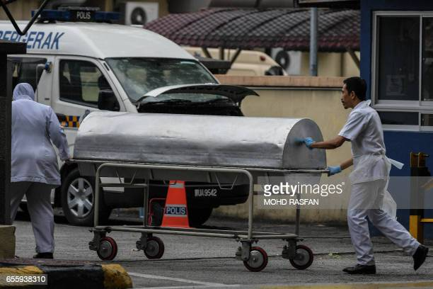 Hospital workers move a body cart to the gate of the forensics wing of the Hospital Kuala Lumpur where the body of Kim JongNam is being held in Kuala...