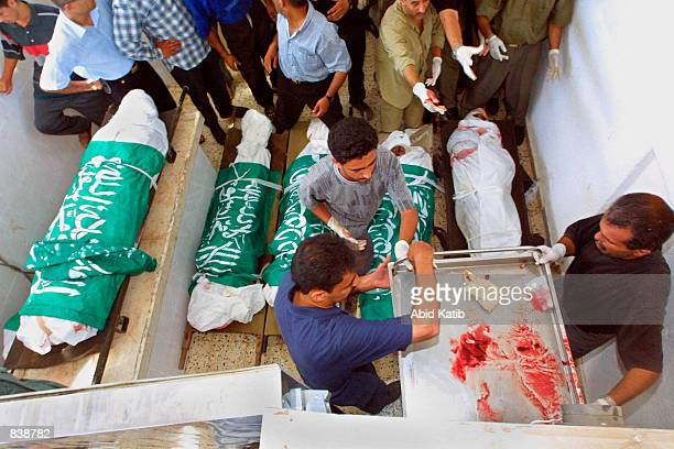 Hospital workers prepare bodies for burial of five of six Palestinians killed in an Israeli missile attack June 24, 2002 in the Rafah, Gaza Strip....