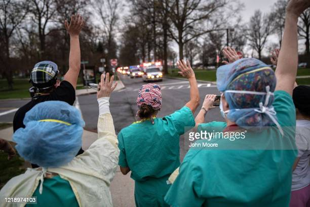 Hospital workers wave and cheer outside the Westchester Medical Center as first responders pass by in a caravan of sirens and lights on April 14 2020...