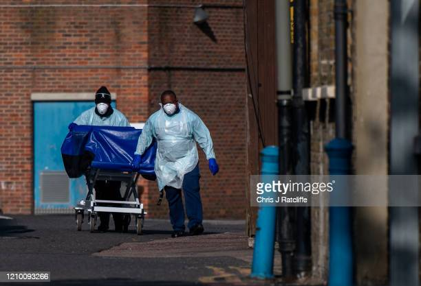 Hospital workers wheel a concealment trolley, typically used for transporting bodies, to the mortuary at Lewisham Hospital on April 16, 2020 in...