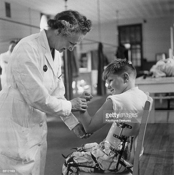 Hospitalised child suffering from polio shows off his biceps to a doctor.