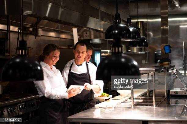 hospitality team discussing bookings on a tablet - restaurant manager stock pictures, royalty-free photos & images